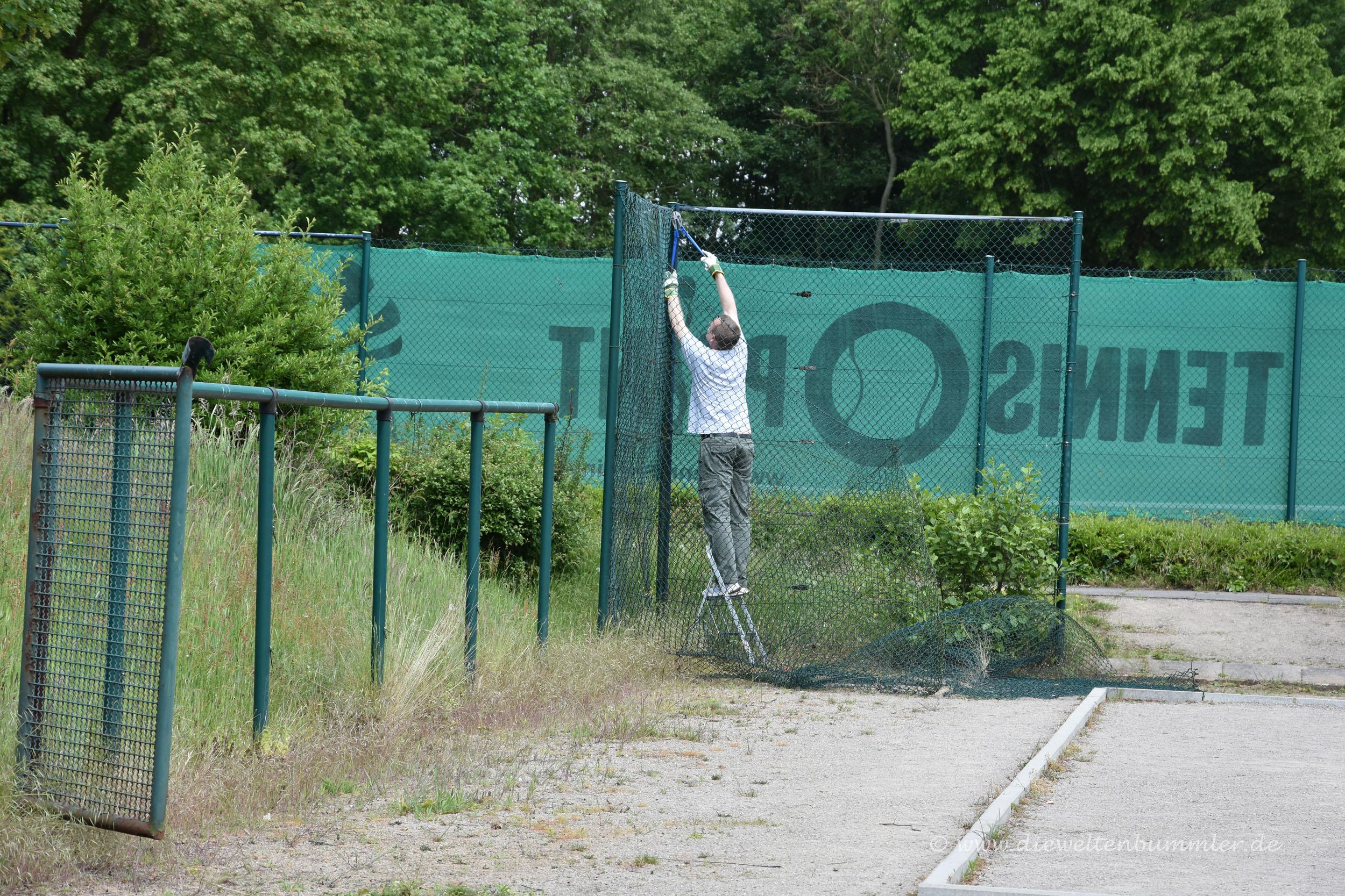 Michael Moll schneidet ein Stück Zaun ab